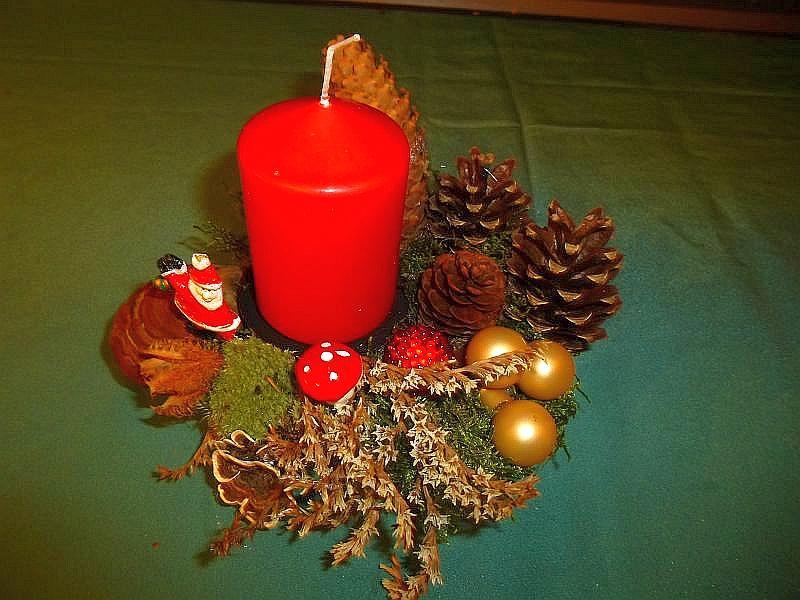 Rundes 1er Gesteck, ca. 15 cm im Durchmesser mit roter Stumpenkerze, Echtem Zunderschwamm, Schmetterlings - Tramete, Moos, Wildkräutern, Kiefern- und Fichtenzapfen sowie Weihnachtsdekoration zu 5,00 €.