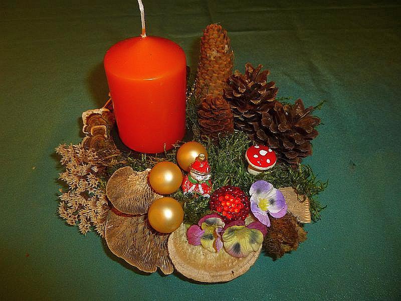 Rundliches 1er Gesteck mit oranger Stumpenkerze, etwa 18 cm im Durchmesser, mir Birken - Blättling, Striegeliger Tramete, Eichen - Wirrling, Schmetterlings - Tramete, Kiefern- und Fichtenzapfen, Moos und Weihnachtsdekoration für 8,00 €.