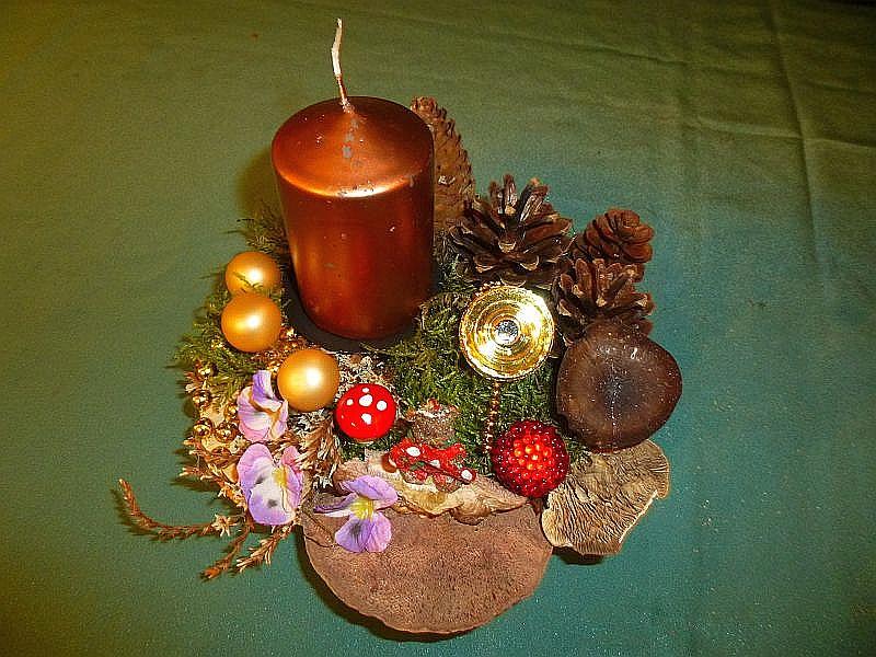 Rundliches 1er Gesteck, ca, 15 cm im Durchmesser, mit goldener Stumpenkerze, Eichen - Wirrling, Rötende Tramete, Birken - Blättling, Winterporling, Moos, Kiefern - und Fichtenzapfen sowie Weihnachtsdekoration zu 8,00 €.