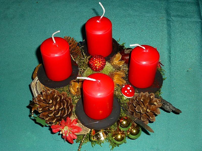 Rundes 4er Gesteck auf Baumscheibe, gut 20 cm im Durchmesser, 4 roten Stumpenkerzen, mit Moos, Schmetterlings - Tramete, Echtem Zunderschwamm, Birken - Blättling, Buchenfruchtschalen, Kastanien, Kiefernzapfen und Weihnachtsdekoration zu 10,00 €.