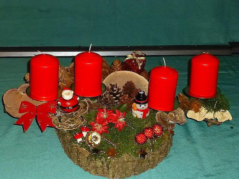 Etwa 50 cm langes und 35 cm tiefes 4er Gesteck mit roten Stumpenkerzen auf Baumscheibe und Ast mit Moos, Rötender Tramete, Schmetterlings - Tramete, Echtem Zunderschwamm, Birken - Blättling, verschiedenen Zapfen und Weihnachtsdekoration zu 25,00 €.
