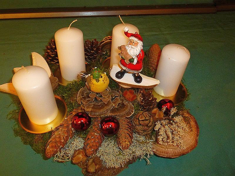 Massives 4er Gesteck mit weißen Stumpenkerzen auf Baumscheibe, gut 40 cm lang und 25 cm tief mit Moos, Birenporling, Schmetterlings - Tramete, Rötende Tramete, verschiedenen Zapfen, Vogel und Weihnachtsdekoration für 20,00 €.