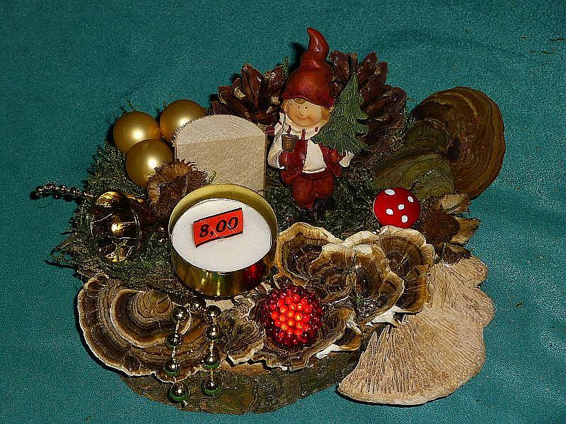 Rundliches Gesteck auf Baumscheibe mit Teelicht, Eichen - Wirrling, Schmetterlings - Tramete, Echtem Zunderschwamm, Moos,Kiefernzsapfen, Holzstück und Weihnachtsdekoration, etwa 18 cm im Durchmesser für 8,00 €.