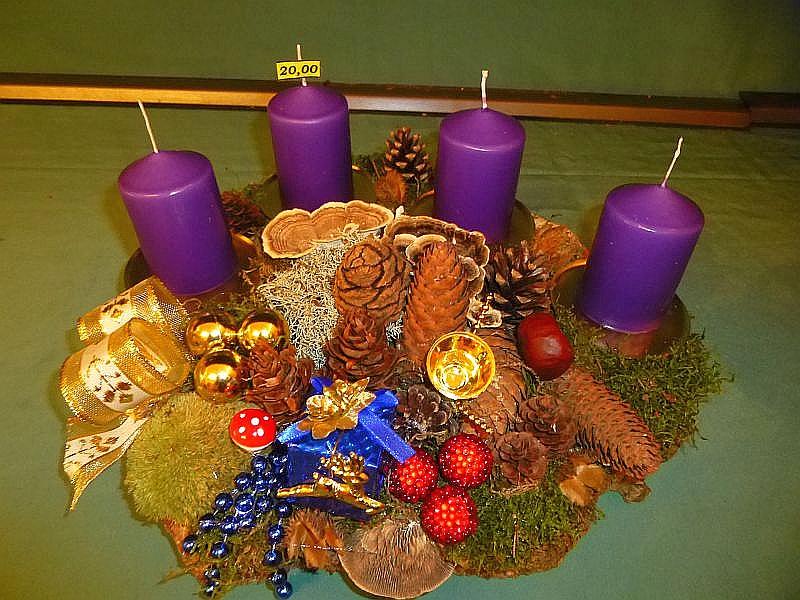 Rundliches 4er Gesteck auf Baumscheibe mit violetten Stumpenkerzen, ca. 35 cm im Durchmesser mit verschiedenen Moosen, Flechten, verschiedenen Zapfen, Kastanien, Birken - Blättling, Eichen - Wirrling, Schmetterlings - Trameten und Weihnachtsdekoration für 20,00 €.