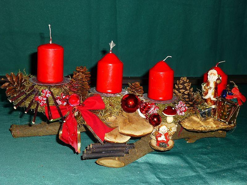 Gut 30 cm langes, 12 cm tiefes 4er Gesteck mit roten Stumpenkerzen auf Ast mit Moos, Kiefernzapfen, Rotrandigem Baumschwamm, Hartriegel mit roter Schleife zu 10,00 €.