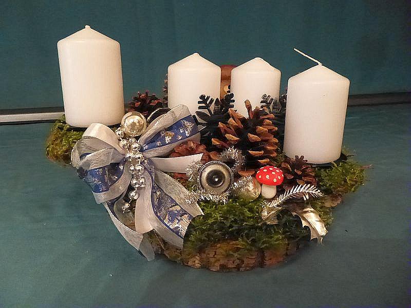 Rundliches 4er Gesteck auf Holzscheibe, mit weißen Stumpenkerzen, Moos, Eichen - Wirrling, Flaschen - Stäubling, Kiefernzapfen und in silber gehaltener Weihnachtsdekoration für 12,50 €.