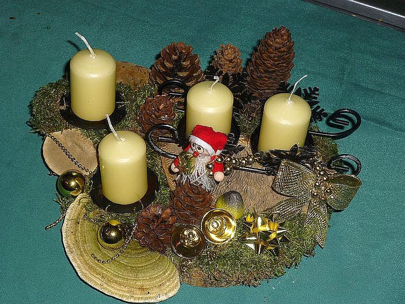Rundliches 4er Gesteck mit chremweißen Stumpenkerzen auf Holzscheibe mit Schlitten, Moos, Striegeliger Tramete, Rotrandigem Baumschwamm, verschiedenen Zapfen, goldener Weihnachtsdekoration zu 12,50 €.