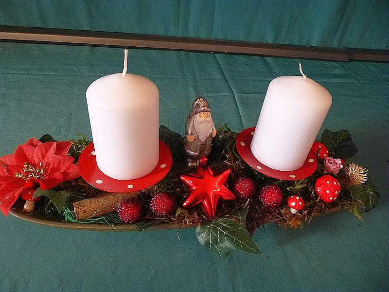 Längliches, etwa 30 cm langes und 10 cm tiefes 2er Gesteck mit weißen Stumpenkerzen aud Schale mit Moos, Holz, künstlichem Efeu, Fliegenpilzchen und Weihnachtsdekoration zu 8,00 €.