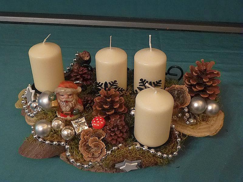 Ovales 4er Gesteck mit weißlichen Stumpenkerzen auf Baumscheibe mit Schlitten, Moos, Kiefernzapfen, Striegeliger Tramete, Schmetterlings - Tramete und vorwiegend silberner Weihnachtsdekoration für 12,50 €.