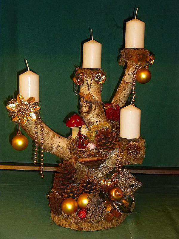 Etwa 50 cm hohes und 35 cm breites 4er Gesteck auf Birken - Gabel mit weißen Stumpenkerzen, goldener Weihnachtsdekoration mit Weihnachtsmann und Kiefernzapfen für 20,00 €.
