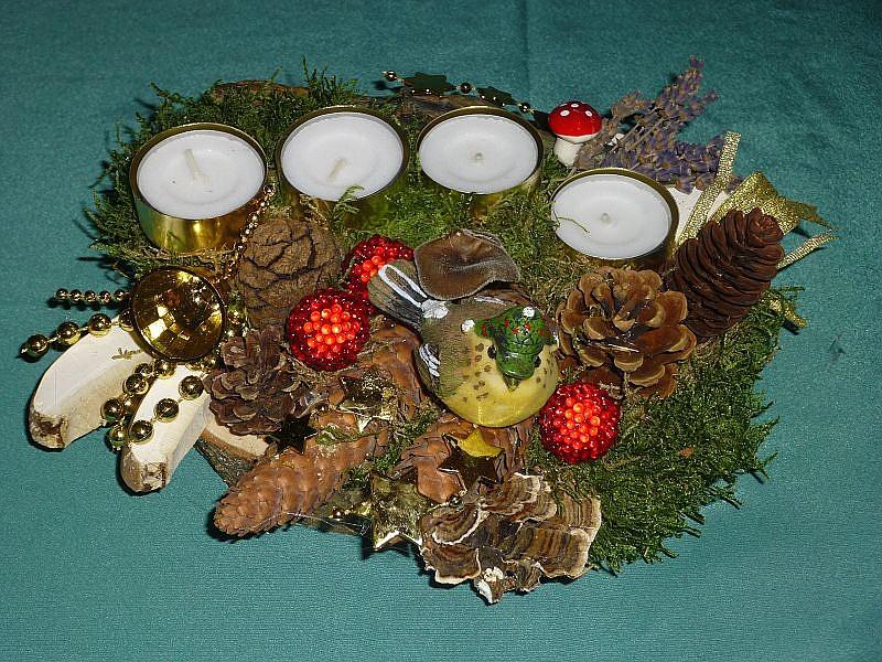 34. - Rundliches 4er Gesteck mit Teelichtern auf Holzscheibe mit Moos, Birken - Porling, Schmetterlings - Tramete, verschiedene Zapfen, Vogel und Weihnachtsdekoration zu 8,00 €.