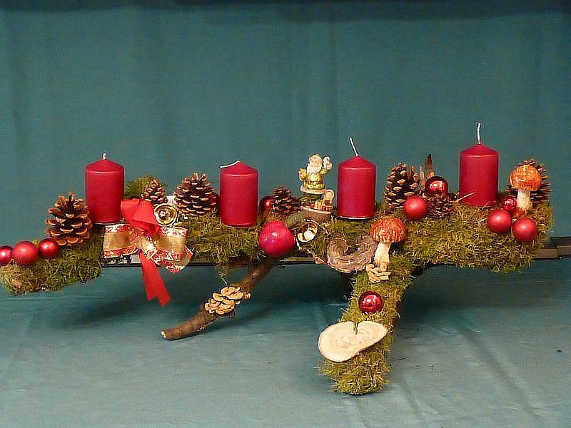 36. - Etwa 70 cm langes, 40,00 cm tiefes und 30 cm hohes 4er Gesteck auf Astgabel mit weinroten Stumpenkerzen, Moos, Kiefernzapfen, Herben Zwergknäuelingen, Schmetterlings - Trameten, Striegeligen Trameten und Weihnachtsdekoration für 20,00 €.