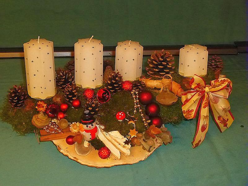 37. - Etwa 50 cm langes und 30 cm tiefes 4er Gesteck mit weißen Sternkerzen auf Ast mit Rotrandigem Baumschwamm, Echtem Zunderschwamm, Striegeliger Tramete, Birkenporling, viel Moos, Kiefernzapfen, Schleife und Weihnachtsdekoration zu 20,00 €.