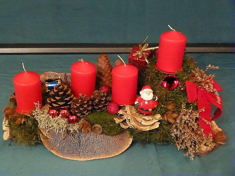 39. - Gut 40 cm langes, 25 cm tiefes, kompaktes 4er Gesteck mit roten Stumpenkerzen auf Ast mit viel Moss, Eichen - Wirrling, Striegeliger Tramete, Schmetterlings - Tramete, Birken - Porling, Kräutern, Kiefern - und Fichtenzapfen, roter Schleife und weiterer Weihnachtsdekoration zu 20,00 €.
