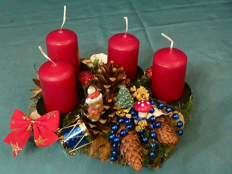 40. Rundes 4er Gesteck mit ca, 20 cm Durchmesser auf Holzscheibe mit weinroten Stumpenkerzen, Moos, Schmetterlings - Tramete, verschiedenen Zapfen und Weihnachtsfekoration für 10,00 €.