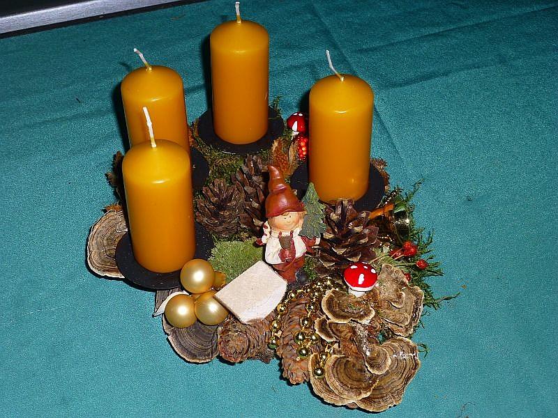 41. - Ovales 4er Gesteck auf Holzscheibe und dunkelgelben Stumpenkerzen mit Moos, Kiefern- und Fichtenzapfen, Schmetterlings - Trameten und dezenter Weihnachtsdekoration zu 10,00 €.