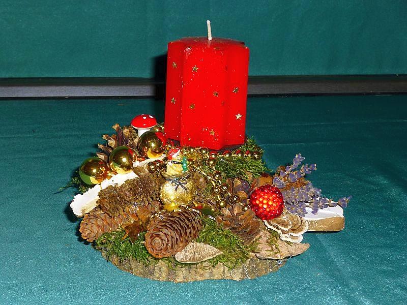 42. - Rundliches 1er Gesteck mit roter Sternkerte, Moos, Schmetterlings - Trameten, geschnettenem Birkenporling, Eichen - Wirrling, verschiedenen Zapfen und Weihnachtsdekoration zu 6,00 €.