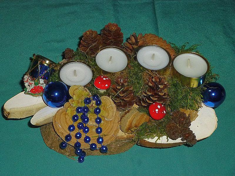 43. - Ovales 4er Gesteck mit Teelichtern auf Holzscheibe mit Moos, Striegeliger Tramete, Echtem Zunderschwamm, geschnittenem Birken - Porling, verschiedenen Zapfen mit Weihnachtsdekoration für 8,00 €.