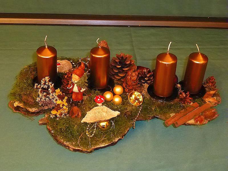 44. - Etwa 40 cm langes und 25 cm tiefes 4er Gesteck auf Ast mit Moos, verschiedenen Zapfen, Kräutern, Striegeliger Tramete, Birken - Blättling, Schmetterlings - Tramete, Birken - Porling, goldenen Stumpenkerzen und Weihnachtsdekoration zu 15,00 €.