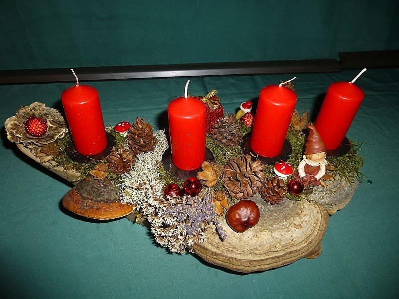 Gut 40 cm langes, 25 cm tiefes 4er Gesteck mit roten Stumpenkerzen, beidseitig dekoriert und stellbar auf Astgasbel mit Rotrandigem Baumschwamm, Echtem Zunderschwamm, Eichen - Wirrlingen, Schmetterlings - Trameten, Moos, Flechten, verschiedenen Zapfen und Weihnachtsdekoration zu 20,00 €.