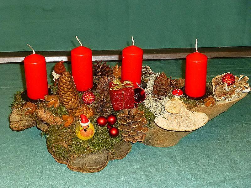 Etwa 40 cm langes und 25 cm tiefes 4er Gesteck auf Astgabel. mit 4 roten Stumpenkerzen, Moos, Eichen - Wirrling, Rotrandigem Baumschwamm, Schmetterlingstramete, Moos, Zapfen, Weihnachtsvogel und weiterer Weihnachtsdekoration für 20,00 €.