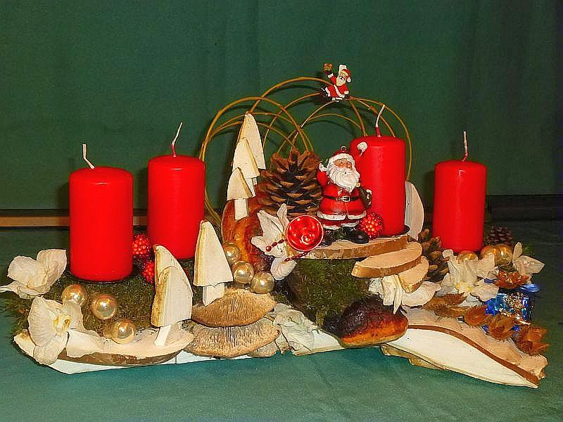 Sehr aufwendiges Edelgesteck auf Astgabel mit 4 roten Stumpenkerzen, Moos, Eichen - Wirrling, Rotrandigem Baumschwamm, Treppe und Tannenbäumen aus Birken - Porlingen mit Zapfen und Weihnachtsdekoration, etwa 50 cm lang und 20 cm tief für 25,00 €.