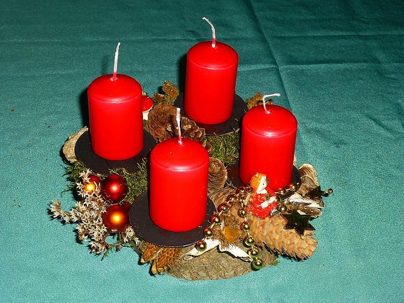 Kleines, rundes 4er Gesteck mit roten Stumpenkerzen auf Baumscheibe mit Schmetterlings - Trameten, Eichen - Wirrlingen, Birken - Porling, Zapfen und Weihnachtsdekoration zu 8,00 €.