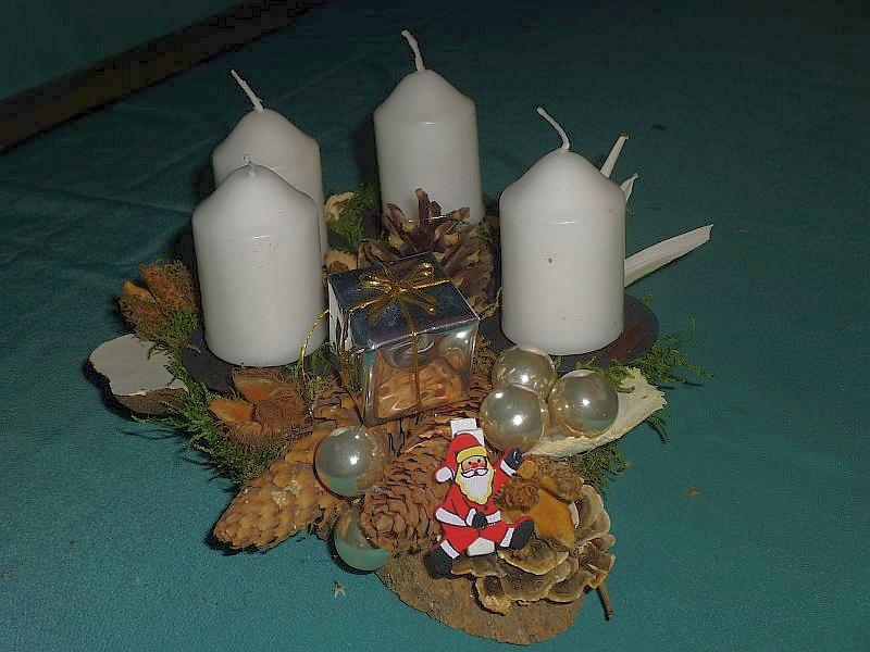 Ovales 4er Gesteck mit weißen Stumpenkerzen auf Holzscheibe mit Moos, Kiefern- und Fichtenzapfen, Schmetterlings - Tramete, Herben Zwergknäuelingen, Birken - Porlingen und Weihnachtsdekoration zu 8,00 €.