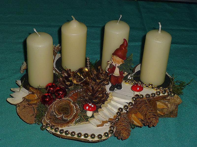 Ovales, knapp 30 cm langes und 20 cm tiefers 4er Gesteck mit weißen Srtumpenkerzen auf Holzscheibe mit Rötender Tramete, Schmetterlings - Tramete, Birken - Porling und Treppe aus Birkenporlingen mit verschiedenen Zapfen und Weihnachtsdekoration zu 12,50 €.