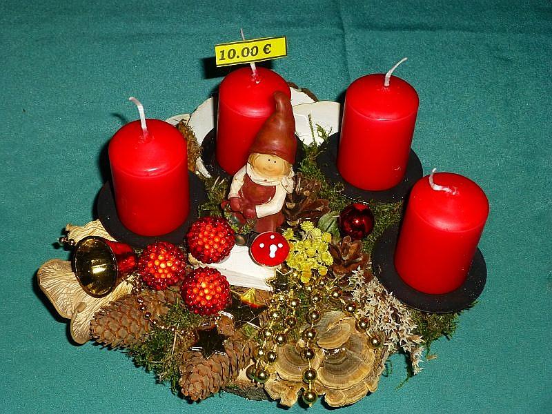 Rundliches 4er Gesteck auf Holzscheibe mit roten Stumpenkerzen, Moos, geschnittenen Birkenporlingen, Birken - Knäuelingen, Schmetterlings - Trameten, Kräutern, verschiedenen Zapfen und Weihnachtsdekoration zu 10,00 €.