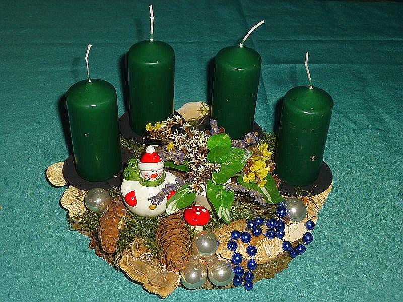 Rundliches 4er Gesteck mit grünen Stumpenkerzen auf Holzscheibe mit Moos, Striegeliger Tramete, Echtem Zunderschwamm, Birken - Blättling, Schmetterlings - Tramete, Eichen - Wirrling, echten und künstlichen Kräutern b.z.w. Blättern, verschiedenen Zapfen und Weihnachtsdekoration für 10,00 €.