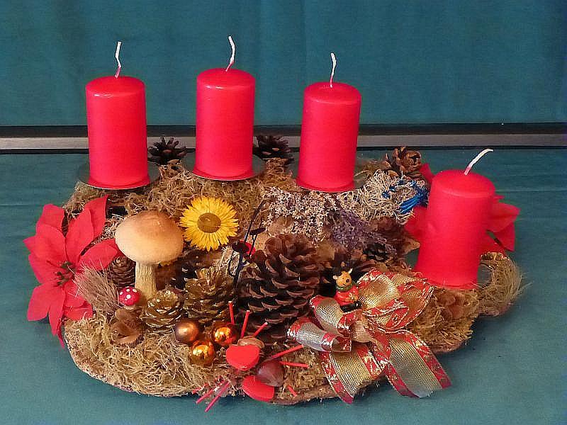 44. - Etwa 40 cm breites und 30 cm tiefes 4er Gesteck auf Rotrandigem Baumschwamm mit roten Stumpenkerzen, Moos, Flechten, Kiefrnzapfen, Strohblumen und Weihnachtsdekoration zu 12,50 €.