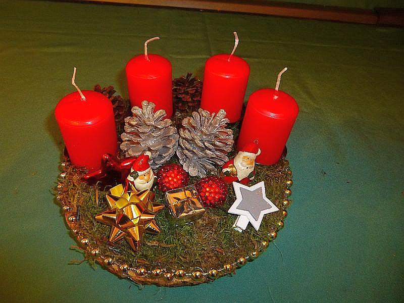 56. - Rundes 4er Gesteck auf Holzscheibe, roten Stumpenkerzen, Moos, teils versilberten Kiefernzapfen und Weihnachtsdekoration zu 10,00 €.