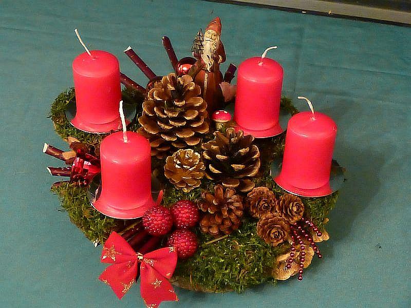 57. - Rundliches 4er Gesteck auf Holzscheibe mit viel Moos, Hartriegel, Zapfen, Birken - Blättling, etwa 30 cm im Durchmesser mit Weihnachtsdekoration zu 15,00 €.