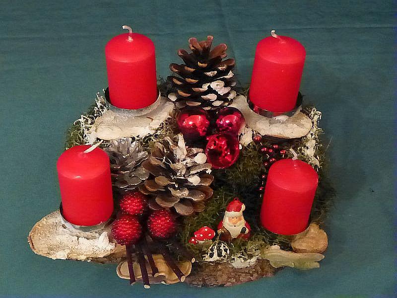 59. - Quadratisches 4er Gesteck auf Holzscheibe mit roten Stumpenkerzen, Moos, Schnee, Kiefernzapfen, ca. 25 cm im Durchmesser, mit Striegeliger Tramete und Weihnachtsdekoration zu 10,00 €.