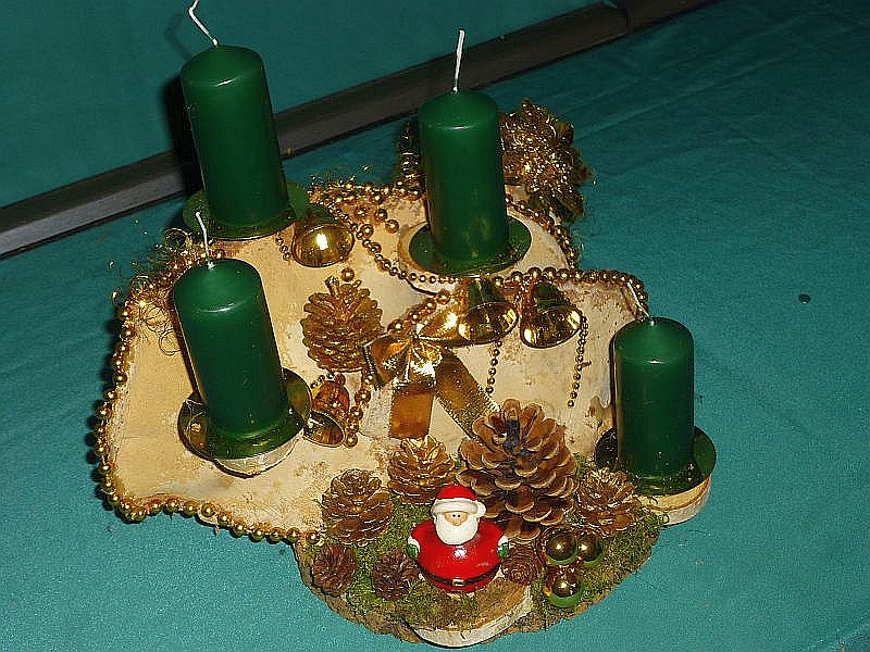 Kompaktes 4er Gesteck auf Holzscheibe mit doppeltem Rotrandigem Baumschwamm, Moos, Kiefernzapfen, grünen Stumpenkerzen und vorwiegend goldener Weihnachtsdekoration, etwa 30 cm breit und jeweils 25 cm tief und hoch zu 15,00 €.