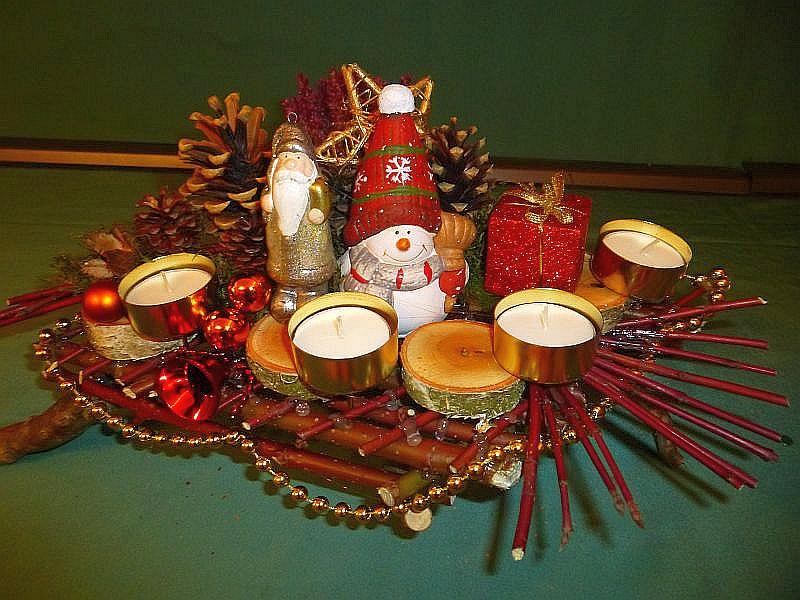 Sehr filigranes 4er Gesteck mit Teelichtern auf Ast mit Hartriegelfächer und Gerüst, Kiefernzapfen, Birkenscheiben und reichlich Weihnachtsdekoration, 35 cm breit und 25 cm tief für 20,00 €.