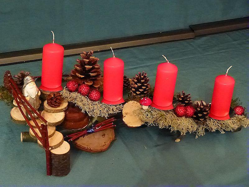 Etwa 45 cm langes, bis 25 cm tiefes 4er Gesteck mit roten Stumpenkerzen auf Astgabel mit Holztreppe, Hartriegelgeländer, Echten Zunderschwamm, Rotrandigem Baumschwamm, Eichen - Wirrling, Moos, vielen Flechten, Kiefernzapfen und Weihnachtsdekoration für 15,00 €.