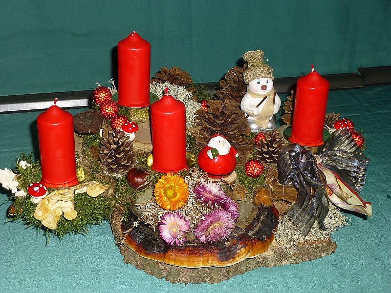 Großes massiges 4er Gesteck auf Holzscheibe mit etwa 50cm Durchmesser, Rotrandigem Baumschwamm, Echtem Zunderschwamm, Schmetterlings - Tramete, Moos, Flechten, Zapfen, Strohblumen, goldener Schleife, Figuren und weiterer Weihnachtsdekoration zu 30,00 €.