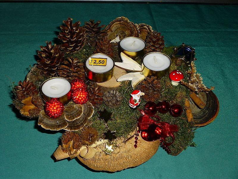 Gut 30 cm im Durchmesser mit 4 Teelichtern auf Holzscheibe mit Echtem Zunderschwamm, Eichen - Wirrling, Rotrandigem Baumschwamm, Moos, Schmetterlings - Trameten, Zapfen, Birkenporling und Weihnachtsdekoration zu 12,50 €.
