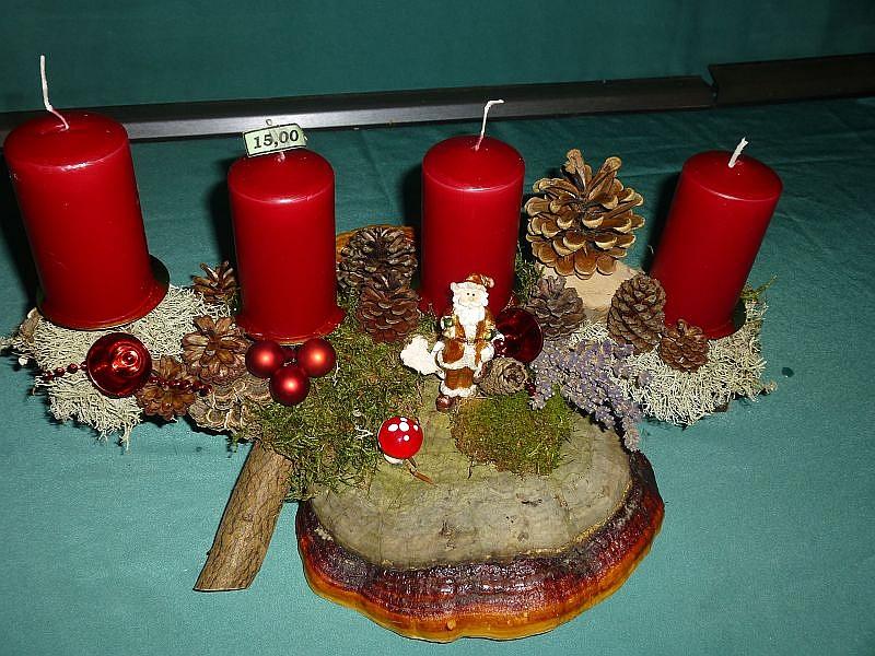 Gut 40 cm langes 4er Gesteck auf Ast mit Moos, Rotrandigem Baumschwamm, Flechten, Kiefernzapfen und weinroten Stumpenkerzen sowie Weihnachtsdekoration zu 15,00 €.