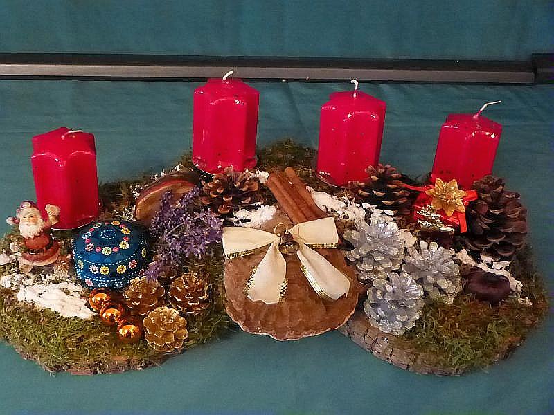 Etwa 50 cm langes und 20 cm tiefes 4er Gesteck auf drei Holzscheiben mit roten Stumpenkerzen, Kiefernzapfen, Moos, Flechten, Flachem Lackporling, Rotrandigem Baumschwamm und Weihnachtsdekoration zu 20,00 €.
