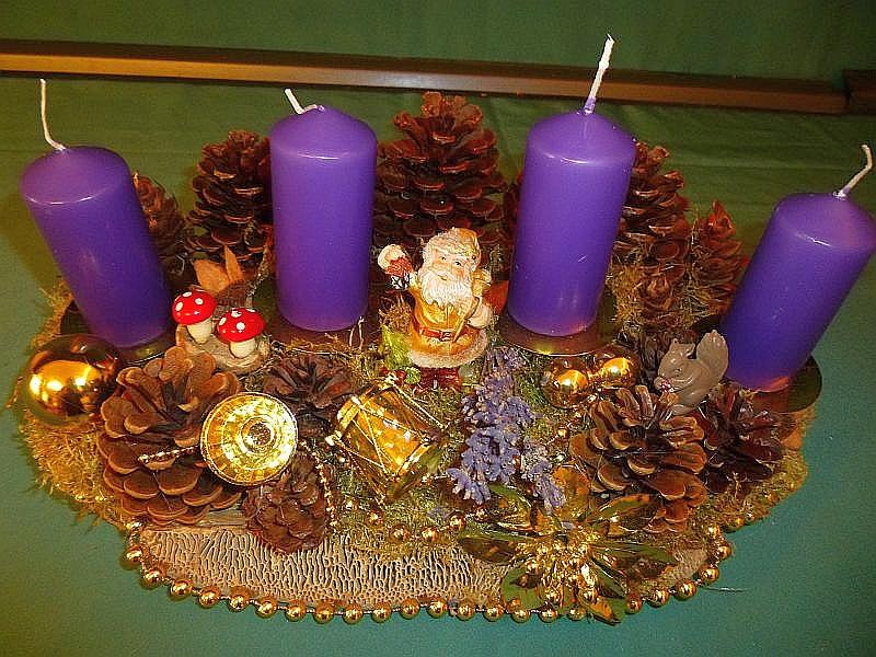 Etwa 40 cm langes und 25 cm breites 4er Gesteck auf Holzscheibe mit violetten Stumpenkerzen, Eichen - Wirrling, Rotrandigem Baumschwamm, vielen Kiefernzapfen, goldener Perlenkette und weiterer in gold gehaltener Weihnachtsdekoration für 15,00 €.