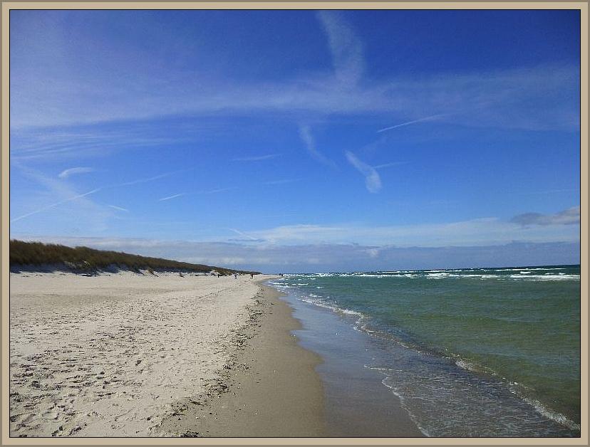 Seicht rollen die weißen Schaumkronen der Wellen am Strand aus.