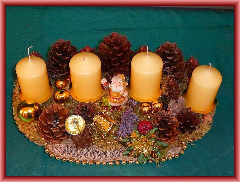 3. Ovales, ca. 35 cm langes und 20 cm tiefes 4er Gesteck mit cremefarbenen Stumpenkerzen auf Eichenwirrling und Holzscheiben, vielen Kiefernzapfen und goldener Weihnachtsdekoration zu 15,00 €.