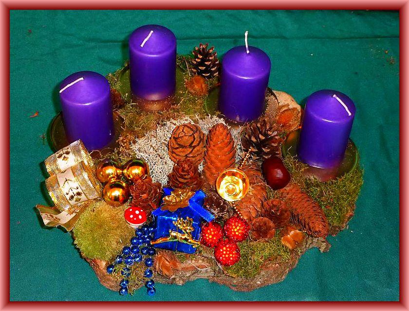 4. Rundliches 4er Gesteck mit violettblauen Stumpenkerzen auf Holzscheibe mit Moos, Eichenwirrling, verschiedenen Zapfen und Weihnachtsdekoration zu 15,00 €.