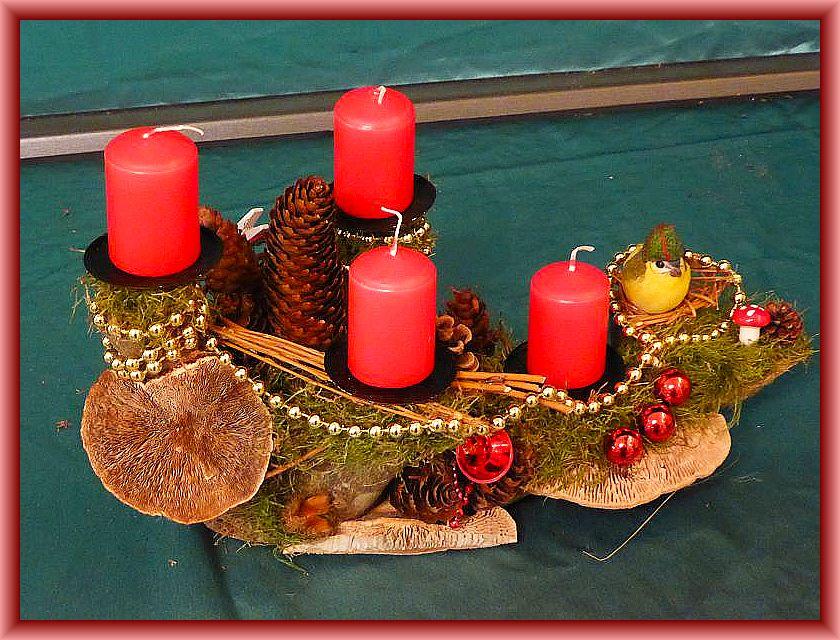 6. Gut 30 cm langes, 15 cm tiefes 4er Gesteck mit roten Stumpenkerzen auf Astgabel mit Moos, Eichenwirrling, Rötende Tramete, Zapfen, Vogelnest, Weihnachtsdekoration und silberner Perlenkette zu 10,00 €.