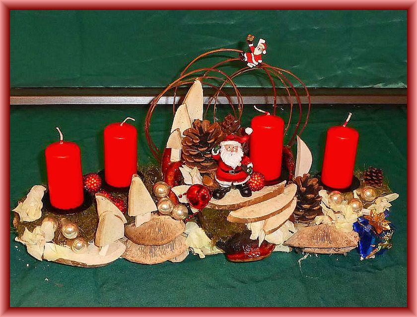 7. Gut 40 cm langes, bis 15 cm tiefes 4er Gesteck mit roten Stumpenkerzen auf Holzunterlage mit Moos, Eichenwirrling, Rotrandigem Baumschwamm, Zapfen, Tannenbäumen aus Birkenporlingen, Weihnachtsmann und weiterer Weihnachtsdekoration für 15,00 €.