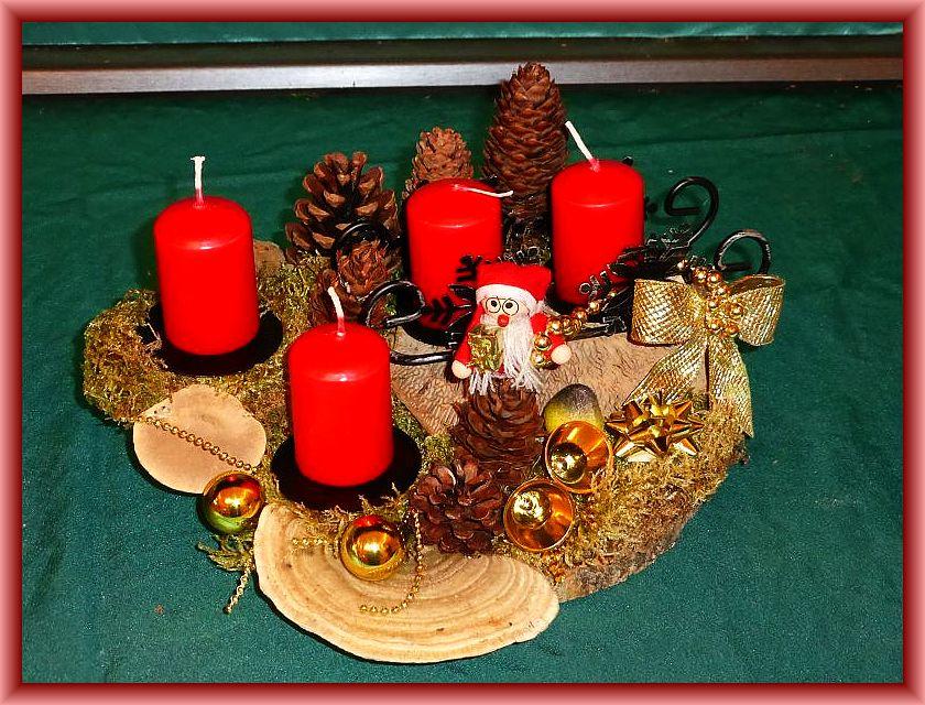 8. Rundliches 4er Gesteck mit roten Stumpenkerzen, Schlitten auf Holzscheibe mit Eichenwirrling, Striegeliger Tramete, Moos, Zapfen, Weihnachtsmann und weiterer Weihnachtsdekoration zu 10,00 €.