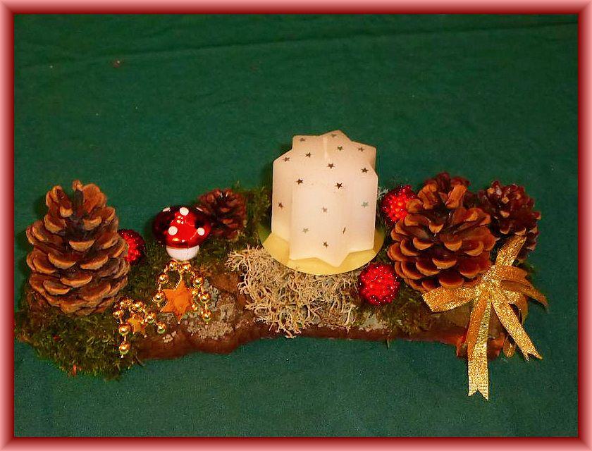10. Etwa 25 cm langes, 8 cm tiefes 1er Gesteck mit weißer Sternenkerze auf Baumrinde mit Kiefernzapfen, Moos und Rentierflechte sowie dezenter Weihnachtsdekoration zu 8,00 €.